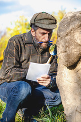 Scientific historian examines through magnifying glass stone sculpture on mound