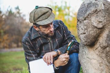 Scientific historian examines through magnifying glass stone sculpture on mound