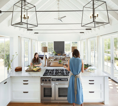 Girlfriends cooking in kitchen of modern design home