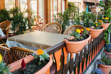 View of empty open summer cafe with wicker chairs and wooden furniture next to pots with plants and flowers.