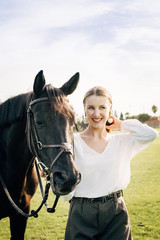 Young woman smiling with her horse
