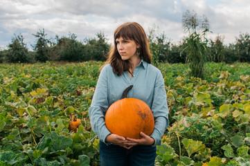 girl holding a pumpkin in a pumpkin patch