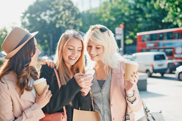Friends shopping together and using smart phone