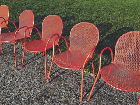 Row of bright red metal chairs and grass