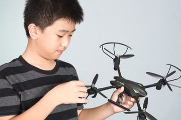 Asian boy holding and checking his hexacopter drone or quadrocopter toy in hand.