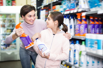 Cheerful woman with daughter choosing cleaners