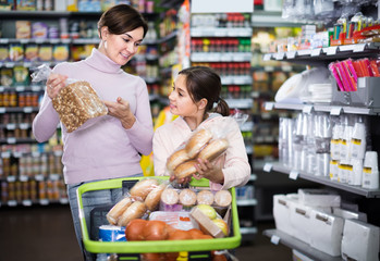smiling woman with daughter choosing bread in supermarket