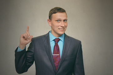 Young successful and smiling business man in suit showing with his index finger up to something copy space. Contact us. Have a new idea concept.