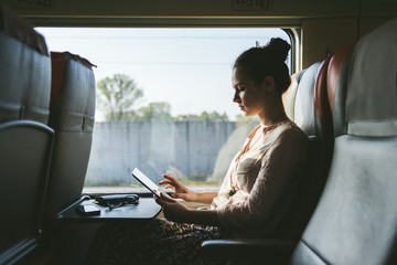 Woman using a tablet sitting in the train
