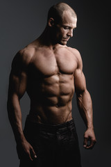 Muscular young man standing against black background