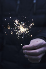 Man holding sparkler in his hand