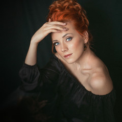 Portrait of redhead woman with blue eyes wearing black dress on dark background. Girl looks directly into the camera.