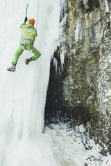 Ice climbing in the mountains along the waterfall.
