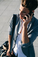 Young man talking with his phone in a street