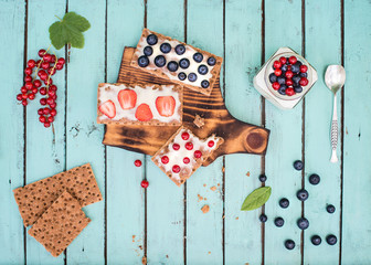 Healthy breakfast. Sandwiches with soft cheese and berries on bread crisps and yoghurt. Healthy eating and summer gifts concept. Creative food.