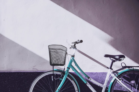 Front of a white and blue bicycle with the basket leaning against the bright purple wall