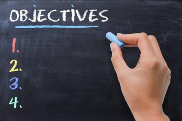 Define business or strategic objectives written by woman on chalkboard