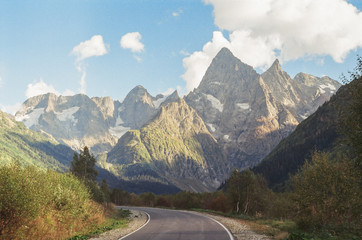 film photography of the mountain landscape in the summer with the paved road