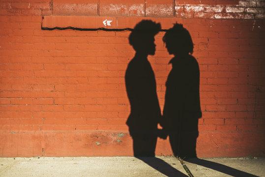 Gay couple shadow on brick wall