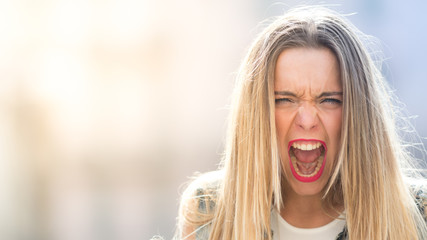 Angry and screaming young girl, portrait photo with copy space
