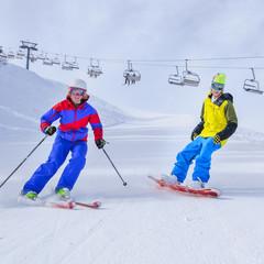 Skifahrerin und Snowboarder auf präparierter Piste