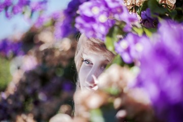 Portrait of a beautiful woman with blue eyes in pink flowers