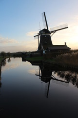 Dutch windmill in evening sun reflects in water