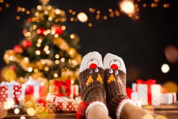 Wall Murals Christmas Detail of woman legs with knitted socks, Christmas tree with gifts on background