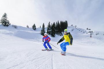 Skifahrerin und Snowboarder gemeinsam auf der Piste unterwegs