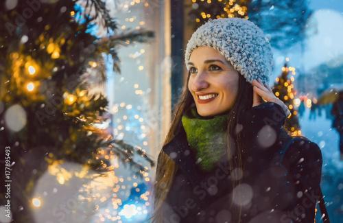 Frau schaut in ein laden schaufenster an weihnachten for Laden schaufenster