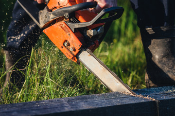 Strong man saws wood with orange chainsaw