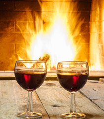 Two Glasses  of  red wine  and  woolen things near  cozy fireplace, in country house, winter vacation, vertical.