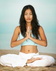 Asian Woman in Prayer Pose on Beach