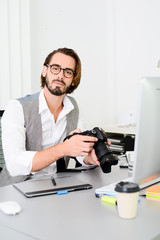 male photographer editing photography in office with a computer, camera and graphic tablet