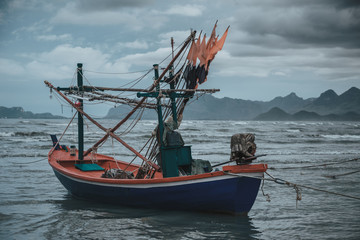 Coastal fishing boats at low tide in summer of Thailand