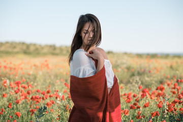 beautiful girl in a poppy field at sunset. concept of freedom