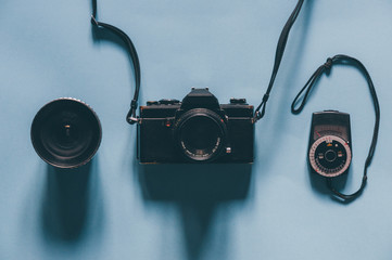 Vintage camera with lens and light meter on blue background, lit by natural light