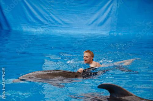 happy man swim with dolphin in dolphinarium