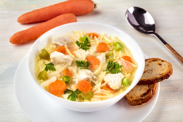 Closeup of chicken soup with noodles, bread, and carrots