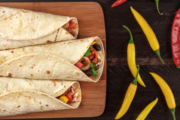 Mexican burritos with chili peppers on dark textures