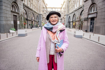 Happy mature woman traveling in town with enjoyment