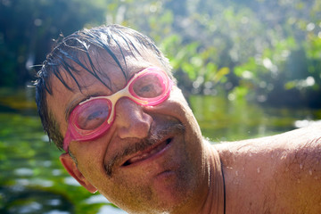 Crazy nerd guy with diving goggles lake