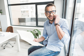 Cheerful smiling man using phone in office