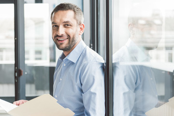 Glad smiling businessman holding papers