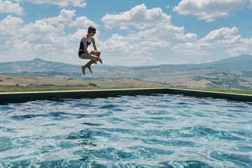 Girl jumping into pool in Italy