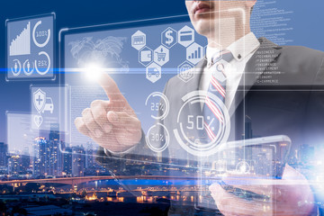 The abstract double exposure image of the business man point to the hologram and cityscape is backdrop. The concept of cashless society, online payment, financial and internet of things.