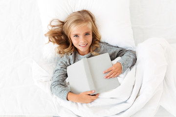 Top view of happy blonde girl lying in bed with gray book, looking at camera