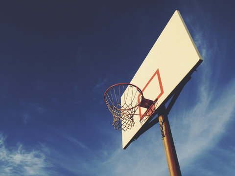 Basketball hoop with blue sky in background, dusk