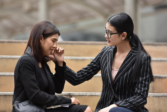 Young Asian Business woman comforting her friend.