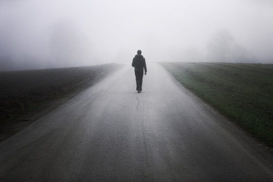 Man walking alone on rural misty asphalt road